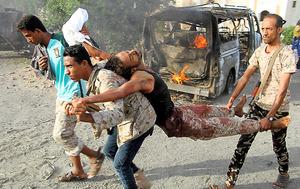 イエメン南部フタで27日、政府の建物などへの自爆攻撃があり、巻き添えになった負傷者を搬送する人々=AFP時事