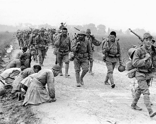 行進する日本軍の傍らで土下座する中国の民衆=1937年11月、中国・江蘇省
