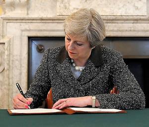28日、EU離脱を通知する書簡に署名する英国のメイ首相=ロイター
