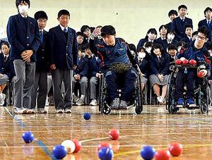 ボールを投げる藤井金太朗選手(中央)。投球を見つめる佐藤駿選手(右)と中学生=2月、東京都練馬区、角野貴之撮影
