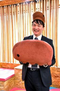 自らがデザインした「クマムシさん」の帽子をかぶり、ぬいぐるみを手にする堀川大樹さん=東京都渋谷区