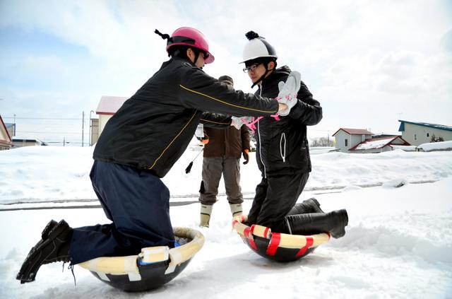 中華鍋押し相撲をする町職員ら。ちょんまげが付いたヘルメットをかぶり、両手を広げられないように手袋がひもでくくられている=新十津川町