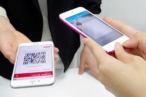 店舗側のスマートフォン(奥)に示されたQRコードを、消費者側のスマホ(手前)で読み取り、ビットコインの決済は完了する(ビットフライヤー提供)
