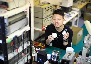 DFreeを手にする。オフィスは大学の部室のような、町工場のような雰囲気だ=東京都渋谷区