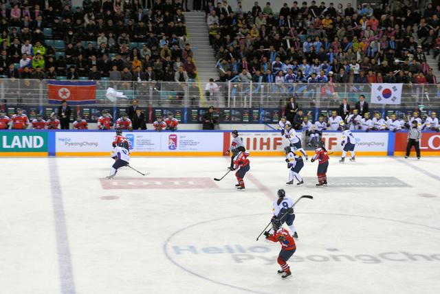 両国の国旗を背に熱戦を繰り広げる韓国と北朝鮮の女子アイスホッケーの選手たち=6日、韓国・江原道江陵市、武田肇撮影