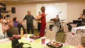 「しあわせすぎキャバレー」で作業療法士の女性と踊る90代の男性参加者。ほかの参加者やスタッフも手拍子で盛り上げた=埼玉県幸手市