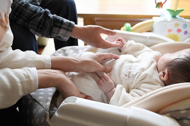 夫妻が伸ばした手を長男が握り返す=大阪府内、伊藤進之介撮影