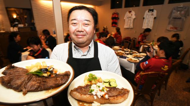ブラジル料理店「ベリンバウ」の渥美リカルド兼治さん。両手にはジーコが好んで注文したというアウトサイドステーキ(左)とイ…