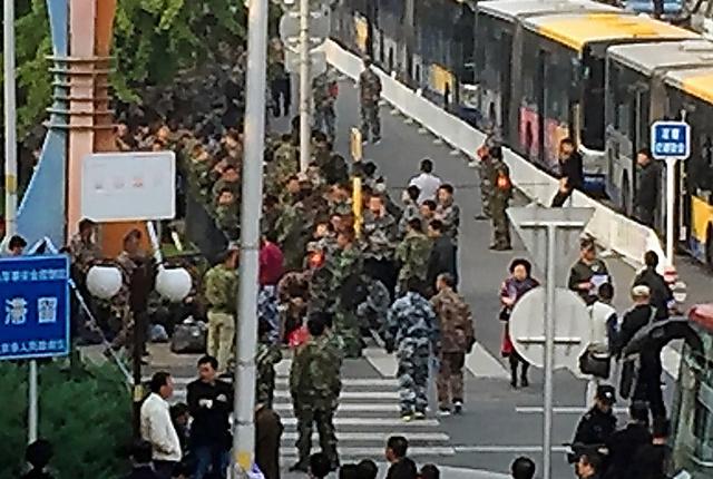 昨年10月、北京の「八一大楼」の周囲を囲んで迷彩服姿で抗議活動をする退役軍人ら=古谷浩一撮影