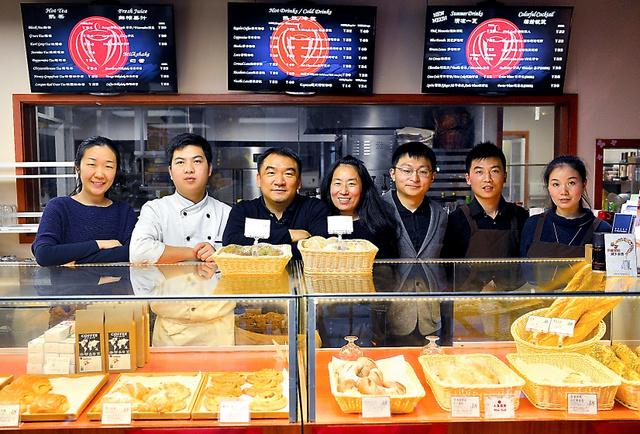 杜聰さん(左から3番目)と、店で働くエイズ孤児のスタッフら。カウンターに自慢のパンが並ぶ=上海市内、冨名腰隆撮影