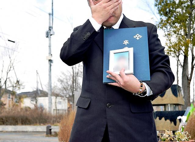 息子が手にするはずだった卒業証書を受け取った父親。2年半たっても悲しみは癒えず、学校近くの献花台で涙があふれた=3月10日、仙台市内、大岩ゆり撮影(写真を一部加工しています)
