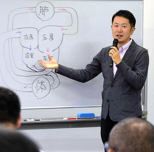 図を描いて、自分の心臓病を説明する猪又竜さん=松本市中央1丁目