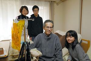 居間のベッドに座る森田さん。妻千香さん、長男浩世さん、長女紗世さんに囲まれて過ごす=3月、東京都内