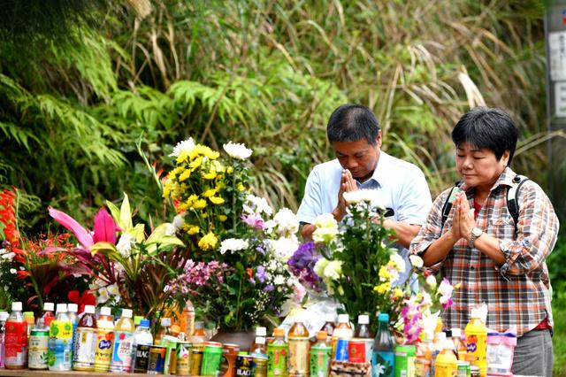 女性の遺体が見つかった現場近くに設けられた献花台で、手を合わせる沖縄県名護市から訪れた小松智さん(左)、瑠美子さん夫妻。智さんは「同じ娘を持つ親として許せない」。瑠美子さんは「米軍基地が無ければ起きなかった事件。忘れてはいけないと思って来ました」と話した=27日午後、沖縄県恩納村、日吉健吾撮影
