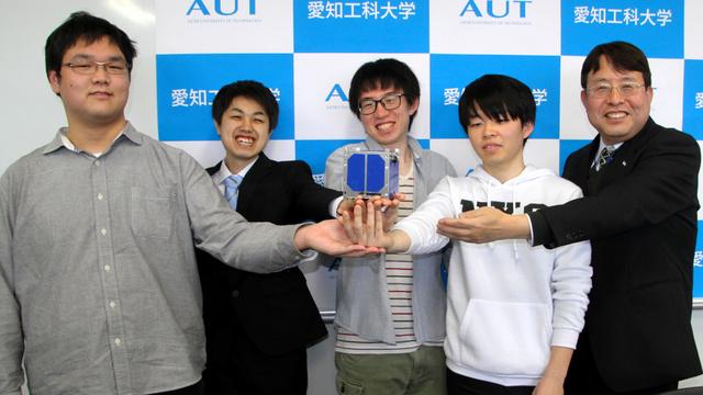 打ち上げる超小型衛星の模型を手にする西尾正則教授(右端)と学生たち=愛知県蒲郡市の愛知工科大学