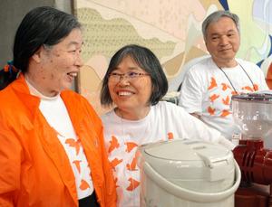 認知症国際会議の会場内にオープンした認知症カフェで、亀尾栄司さん(右)と通子さん(左)は笑顔でカウンターに立った=京都市左京区の国立京都国際会館