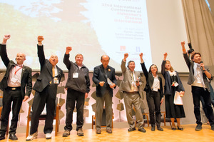 ワークショップの終わりに、国内外の認知症当事者が壇上で「頑張るぞ」と、声を合わせた=京都市左京区の国立京都国際会館
