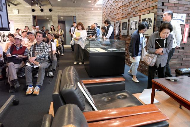 「『みる・きく・はなす』はいま」展が開かれた朝日新聞阪神支局の資料室には大勢の市民が訪れた。手前は事件の時に小尻記者が座っていたソファ=3日午後、兵庫県西宮市、伊藤進之介撮影