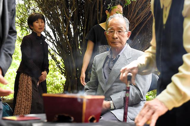 乙女塚の慰霊祭で最前列に座り、焼香の様子を見守る上村好男さん(中央)=熊本県水俣市袋