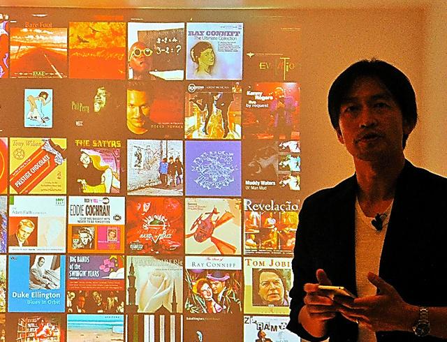 壁一面に現れたCDジャケットを前に説明するソニーの斉藤博さん