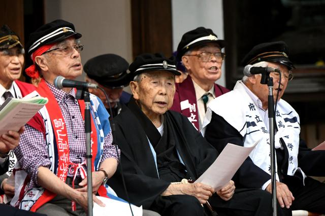 靖国神社の能楽堂で歌う参加者たち。中央は「温知会」代表の岸保芳郎さん=13日午前10時28分、東京都千代田区、角野貴之撮影