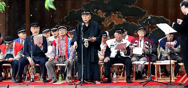 靖国神社の能楽堂で歌う参加者たち。中央は「温知会」代表の岸保芳郎さん=13日、東京都千代田区、角野貴之撮影