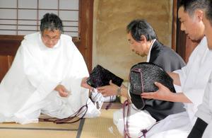 神主役である神殿(こうどの)の交代式「あげもちぶるまい」。紋付きを着た新神殿(左から2人目)に烏帽子が渡された=5月5日、志古淵神社