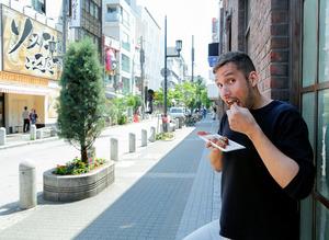 ヨーロッパ村でたこ焼きを食べるスイス人のジョナスさん=大阪市中央区、槌谷綾二撮影