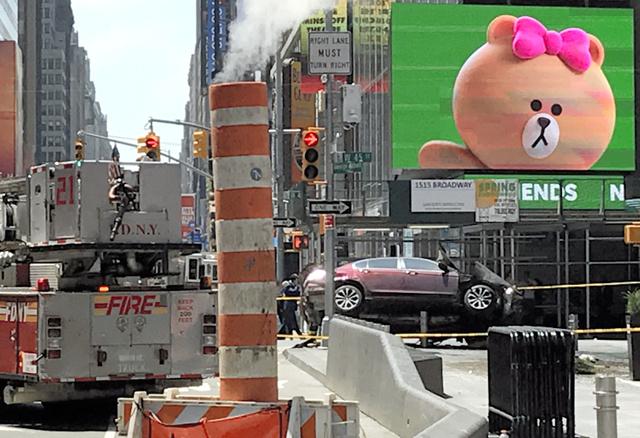 米ニューヨーク・タイムズスクエアの現場。7番街で停車している消防車両の右奥に見えるのが歩道に突っ込んだ車。右側の前部が大破している=18日午後0時31分、金成隆一撮影