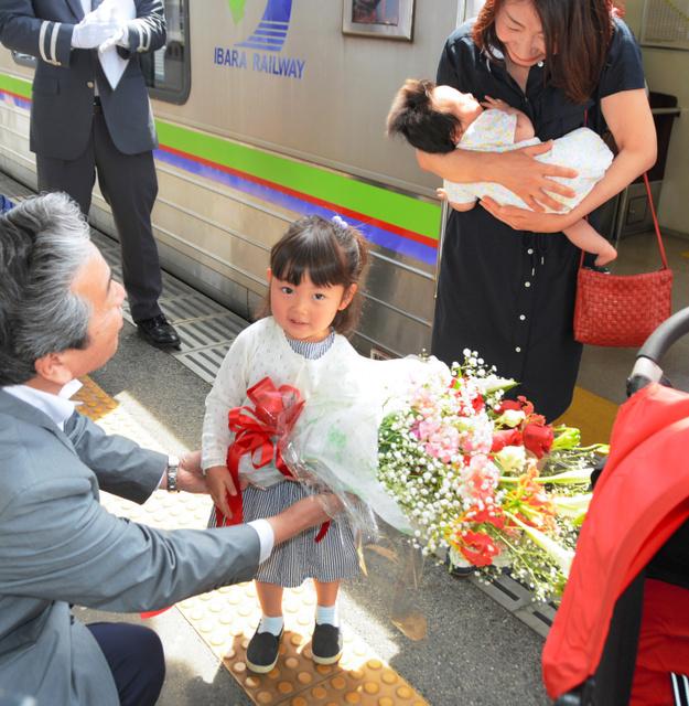 2千万人目の乗客になり、花束を贈られる高原千佳ちゃん=井原駅