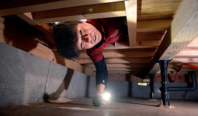 診断する住宅はくまなく見て回る。戸建ての床下を診るときは、体をよじらせて潜り込む。「家の健康診断のような仕事です」=東京都杉並区、浅野哲司撮影