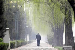 北京で濃いもやの中を歩く高齢の男性=ロイター