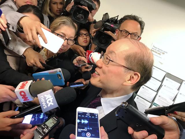 国連安全保障理事会で対北朝鮮制裁の行方のカギを握る中国の劉結一・国連大使が議場から出てくると報道陣が殺到。エスカレーター前まで追いかけると、劉氏は時折笑顔も見せながら話し始めた=23日、米ニューヨーク、金成隆一撮影