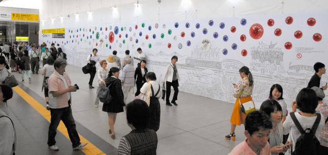 開通してにぎわうJR広島駅の南北自由通路の壁画アート前=広島市南区