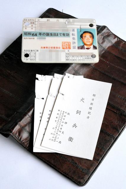 犬飼兵衛記者が上着のポケットに入れていた財布。中にあった運転免許証と名刺にも被弾した跡がある=兵庫県西宮市、水野義則撮影(画像を一部加工しています)
