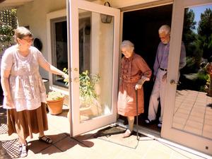 庭に出て散歩をするグレッタ・ノォップさん(中央)。長女のウラさん(左)と夫のウィリーさんが付きそう=米国・ソノマ