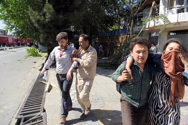 アフガニスタンの首都カブールで31日、自動車爆弾の爆発で負傷した人を助ける男性ら=AFP時事