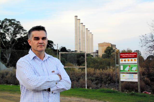 3月末で閉鎖されたヘイゼルウッド火力発電所(後方)の前に立つマーク・リチャーズさん=ラトロブバレー、小暮哲夫撮影