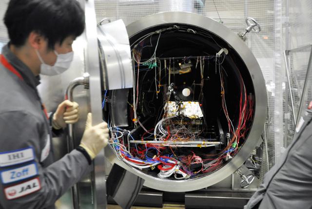 月面の環境を模した円筒形の装置に入れられるソラト=4日午後6時35分、北九州市戸畑区の九州工大・超小型衛星試験センター