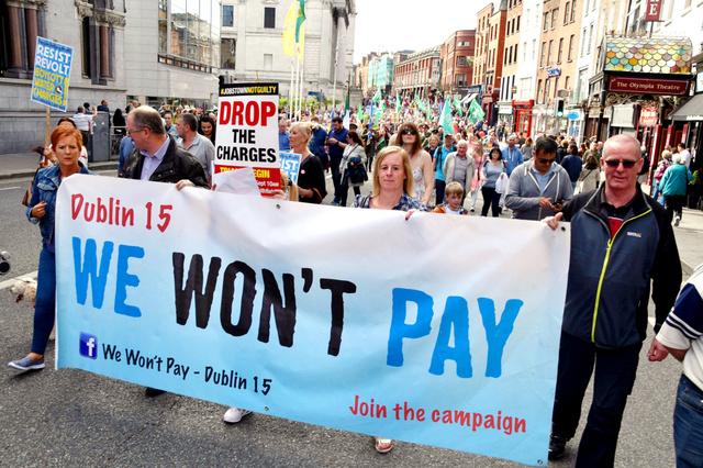 アイルランドで「我々は払わないぞ」と書かれた横断幕をもって歩くデモの参加者。家庭用水道水の有料化に反対していたが、怒りはアップルの「節税」にも向けられた=ダブリン、昨年9月、寺西和男撮影