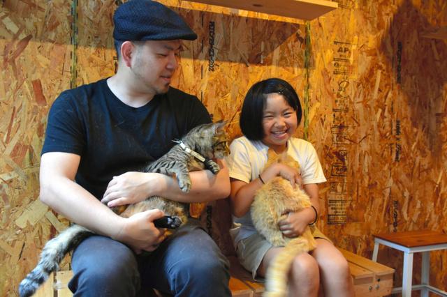 「猫庭」で猫を抱く手島英樹さんと姫萌さん=山口市阿知須