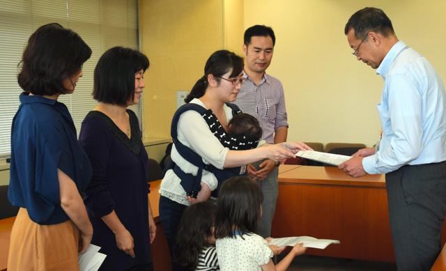 認証保育所存続の陳情書と署名を区に提出する保護者ら=港区役所