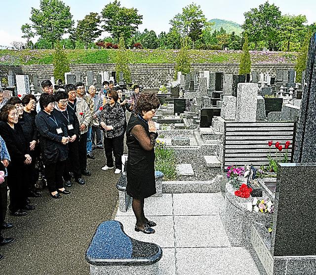 札幌市にあるサハリン残留邦人のための共同墓所で祈る永住帰国者と一時帰国者=5月25日