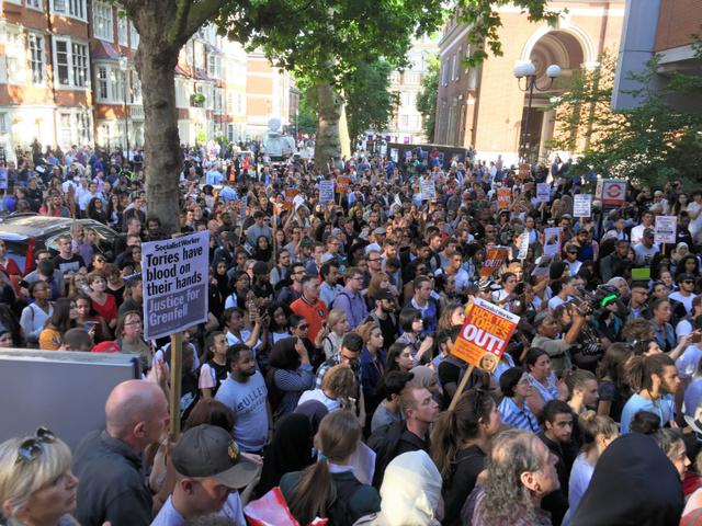 公営住宅の大規模火災を受けて、ロンドン西部ケンジントン・アンド・チェルシー区の区役所前で地元行政や政府に抗議する人たち=16日、渡辺志帆撮影