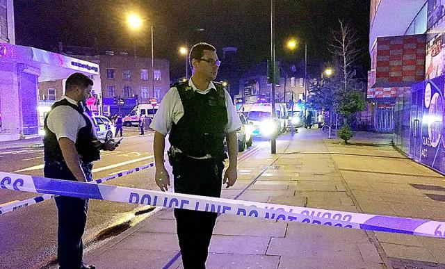 ロンドン北部フィンズベリー・パーク付近で19日、乗用車が歩行者に突っ込んだ現場の周辺を封鎖する警察官=ロイター