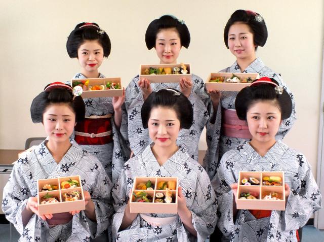 宮川町のビアガーデンで提供される弁当やオードブルを手にする舞妓たち=東山区