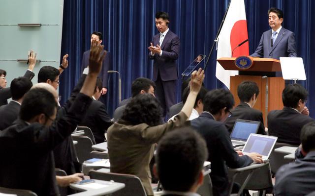 安倍晋三首相(右上)の会見で質問のために挙手をする記者たち=19日午後6時26分、首相官邸、岩下毅撮影