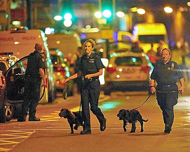 ロンドン北部フィンズベリーパーク近くで19日、乗用車が歩行者に突っ込んだ事件現場を調べる警察官ら=ロイター