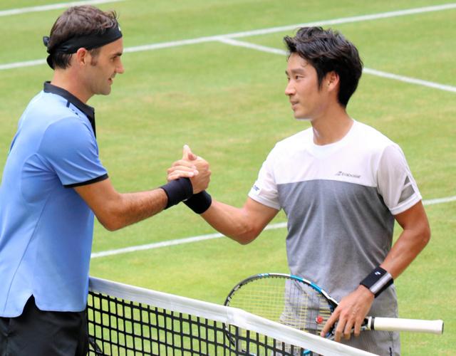 試合に敗れ、フェデラー(左)と握手する杉田=稲垣康介撮影