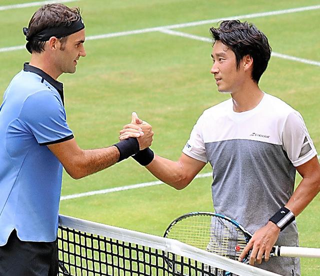 試合に敗れ、フェデラー(左)と握手する杉田